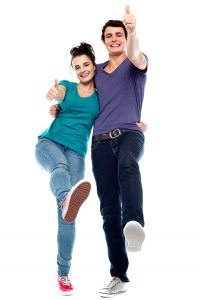 Happy dancing couple gives thumbs up