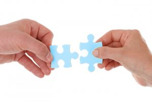 Person fitting puzzle pieces together