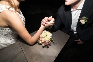 Bride and groom arm wrestling